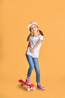 Stylish little girl child girl in casual with skateboard over yellow .