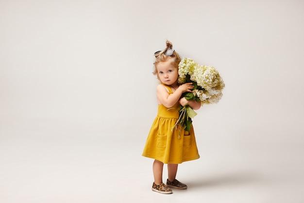 白い背景で分離された野生の花の花束を保持している黄色のドレスのスタイリッシュな女の子。子供のファッション。コピースペース