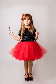 Stylish little girl on red dress holding lollipop and to smiling