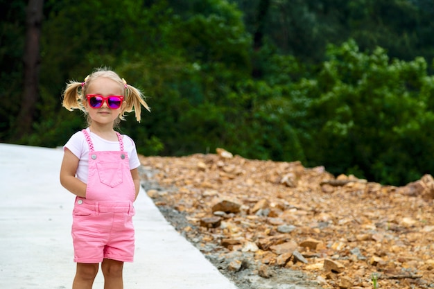 Stylish little girl with blonde hair standing outdoor