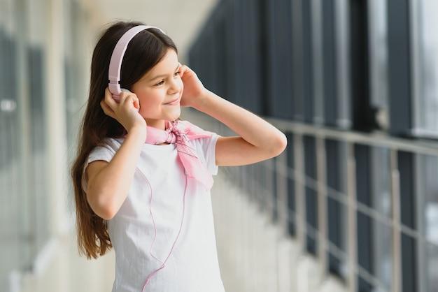 空港でヘッドフォンを持つスタイリッシュな少女