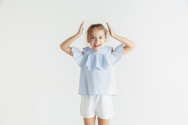 Elegante bambina sorridente in posa in abiti casual isolati su bianco studio