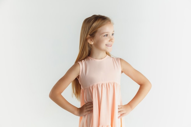 Elegante bambina sorridente in posa in abito isolato su sfondo bianco studio. modello femminile biondo caucasico. emozioni umane, espressione facciale, infanzia. sorridendo, tenendosi per mano su una cintura.