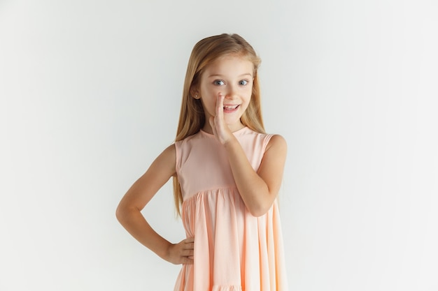 Stylish little smiling girl posing in dress isolated on white studio background. caucasian blonde female model. human emotions, facial expression, childhood. whispering a secret, smiling.