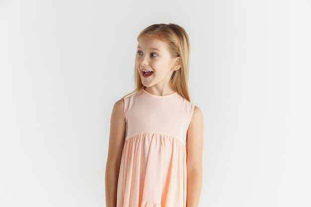 Stylish little smiling girl posing in dress isolated on white studio background. caucasian female model. human emotions, facial expression, childhood. wondered, astonished, shocked. looking at side.