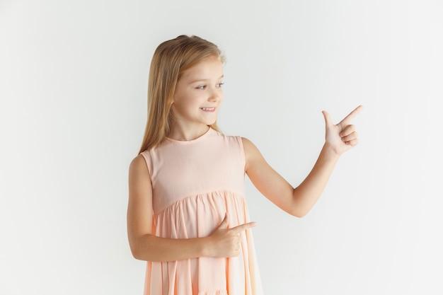 Elegante bambina sorridente in posa in abito isolato su bianco studio