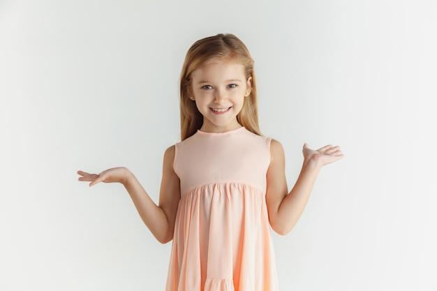 Stylish little smiling girl posing in dress isolated on white wall. caucasian blonde female model. human emotions, facial expression, childhood. smiling, astonished, wondered.