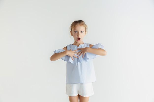 고립 된 캐주얼 옷을 입고 포즈 세련 된 작은 웃는 소녀. 백인 금발 여성 모델. 인간의 감정, 표정, 어린 시절. 놀랐습니다.