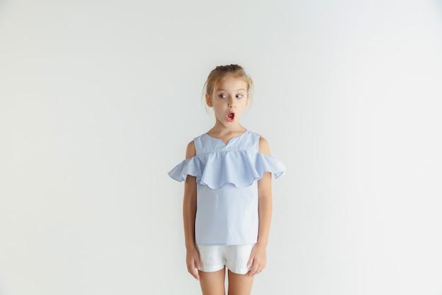 세련 된 작은 웃는 소녀 흰색 배경에 고립 된 캐주얼 옷을 입고 포즈. 백인 금발 여성 모델. 인간의 감정, 표정, 어린 시절. 충격적이고 사려 깊고 측면을 봅니다.