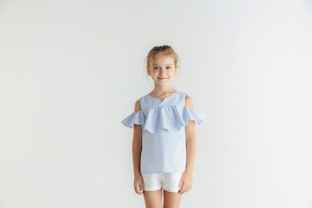 Стильная маленькая улыбающаяся девочка позирует в повседневной одежде, изолированной на белом пространстве. кавказская блондинка женская модель. человеческие эмоции, выражение лица, детство