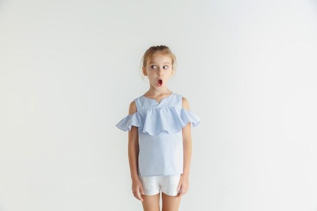 白いスペースに隔離されたカジュアルな服でポーズをとるスタイリッシュな小さな笑顔の女の子。白人の金髪女性モデル。人間の感情、表情、子供時代