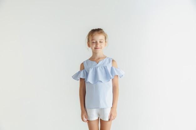 白いスタジオの背景に分離されたカジュアルな服でポーズをとるスタイリッシュな小さな笑顔の女の子。白人の金髪女性モデル。人間の感情、表情、子供時代。目を閉じて夢を見る。