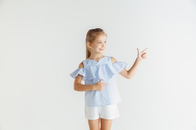 Стильная маленькая улыбающаяся девочка позирует в повседневной одежде на белом фоне студии. кавказская блондинка женская модель. человеческие эмоции, мимика, детство. указывая на пустой пробел.