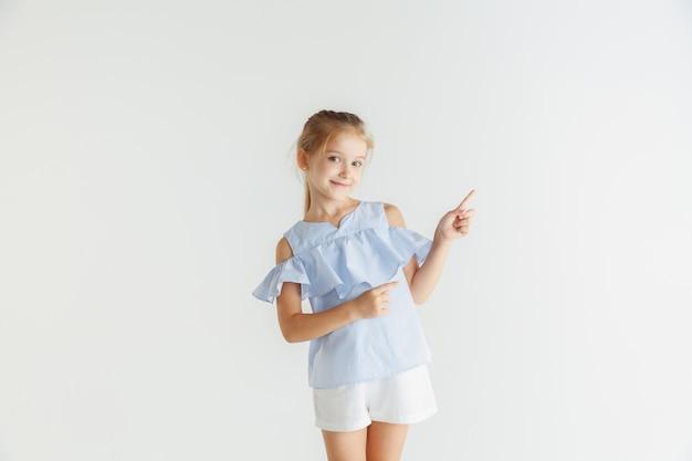 白いスタジオの背景に分離されたカジュアルな服でポーズをとるスタイリッシュな小さな笑顔の女の子。白人の金髪女性モデル。人間の感情、表情、子供時代。空のスペースバーを指しています。
