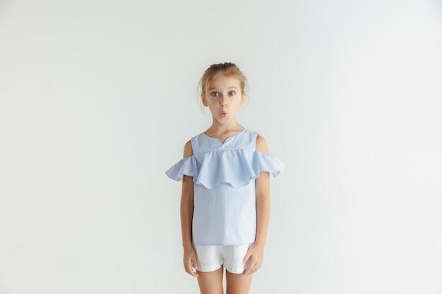 白いスタジオの背景に分離されたカジュアルな服でポーズをとるスタイリッシュな小さな笑顔の女の子。白人の金髪女性モデル。人間の感情、表情、子供時代。ショックを受けた、疑問に思った。
