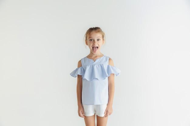 白いスタジオの背景に分離されたカジュアルな服でポーズをとるスタイリッシュな小さな笑顔の女の子。白人の金髪女性モデル。人間の感情、表情、子供時代。笑顔、しかめっ面。