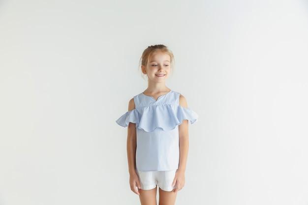 Стильная маленькая улыбающаяся девочка позирует в повседневной одежде на белом фоне студии. кавказская блондинка женская модель. человеческие эмоции, мимика, детство. улыбается, смотрит в сторону.