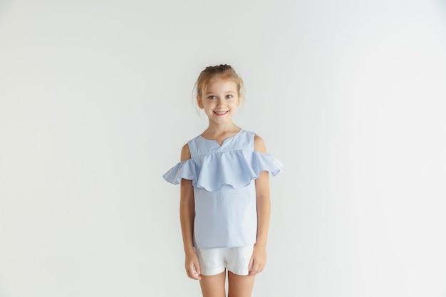 白いスタジオの背景に分離されたカジュアルな服でポーズをとるスタイリッシュな小さな笑顔の女の子。白人の金髪女性モデル。人間の感情、表情、子供時代。立って笑っている。