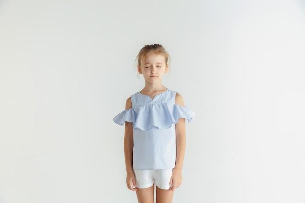 白いスタジオの背景に分離されたカジュアルな服でポーズをとるスタイリッシュな小さな笑顔の女の子。白人の金髪女性モデル。人間の感情、表情、子供時代。目を閉じて立っています。