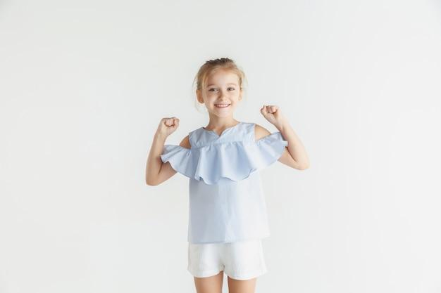 흰색 스튜디오 배경에 고립 된 캐주얼 옷을 입고 포즈 세련 된 작은 웃는 소녀. 백인 금발 여성 모델. 인간의 감정, 표정, 어린 시절. 승리, 축하, 미소.