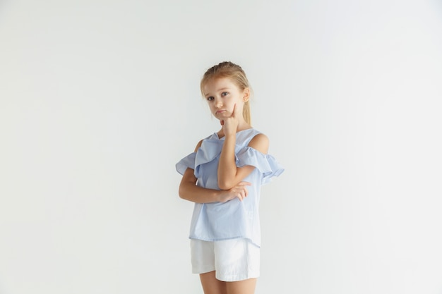 白いスタジオで隔離のカジュアルな服でポーズをとってスタイリッシュな小さな笑顔の女の子