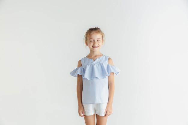 白い壁に隔離のカジュアルな服でポーズをとるスタイリッシュな小さな笑顔の女の子。白人の金髪女性モデル。人間の感情、表情、子供時代。目を閉じて夢を見る。