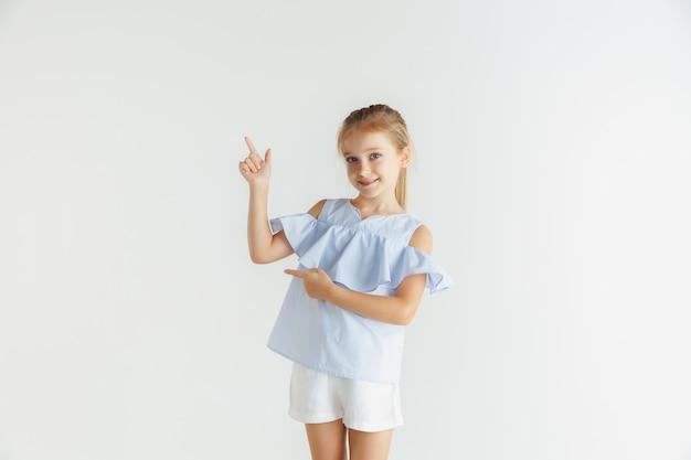 흰 벽에 고립 된 캐주얼 옷을 입고 포즈 세련 된 작은 웃는 소녀. 백인 금발 여성 모델. 인간의 감정, 표정, 어린 시절. 빈 스페이스 바를 가리 킵니다.