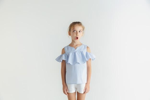 Стильная маленькая улыбающаяся девочка позирует в повседневной одежде, изолированной на белой стене. кавказская блондинка женская модель. человеческие эмоции, мимика, детство. потрясенный, задумчивый, глядя в сторону.