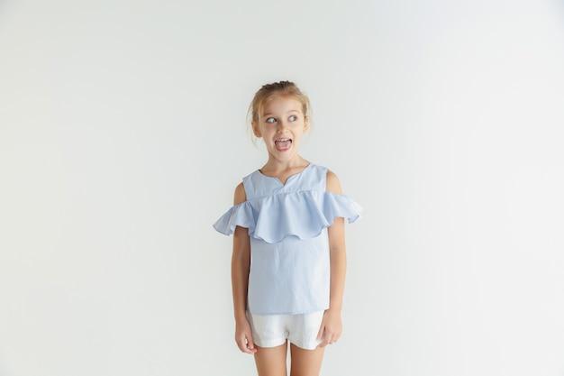 Стильная маленькая улыбающаяся девочка позирует в повседневной одежде, изолированной на белой стене. кавказская блондинка женская модель. человеческие эмоции, мимика, детство. улыбается, безумно смотрит в сторону.