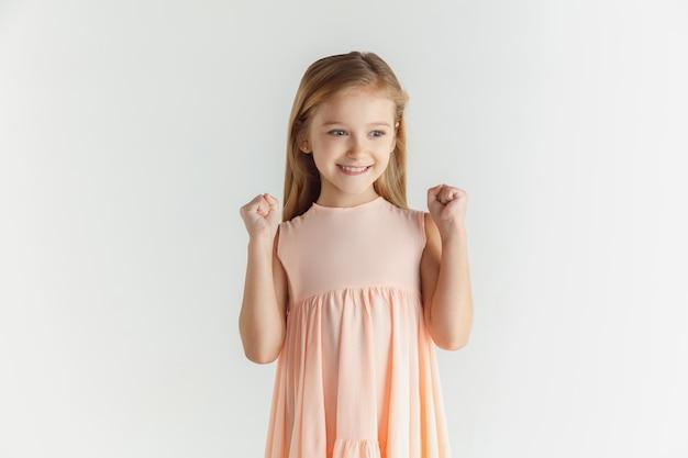 공백에 고립 된 드레스를 입고 포즈를 취하는 세련 된 작은 웃는 소녀. 백인 금발 여성 모델. 인간의 감정, 표정, 어린 시절