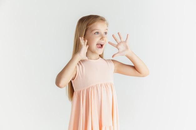 세련 된 작은 웃는 소녀 흰색 스튜디오 배경에 고립 된 드레스에 포즈. 백인 금발 여성 모델. 인간의 감정, 표정, 어린 시절. 전화하고, 놀랐고, 궁금했습니다.