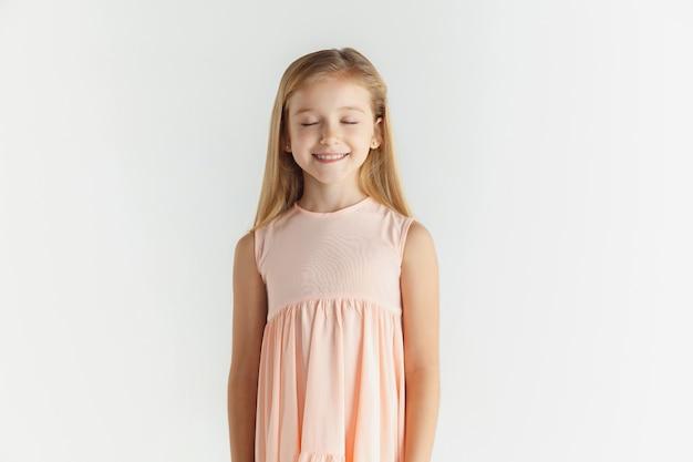 세련 된 작은 웃는 소녀 흰색 스튜디오 배경에 고립 된 드레스에 포즈. 백인 금발 여성 모델. 인간의 감정, 표정, 어린 시절. 눈을 감고 웃고 차분해 보인다.