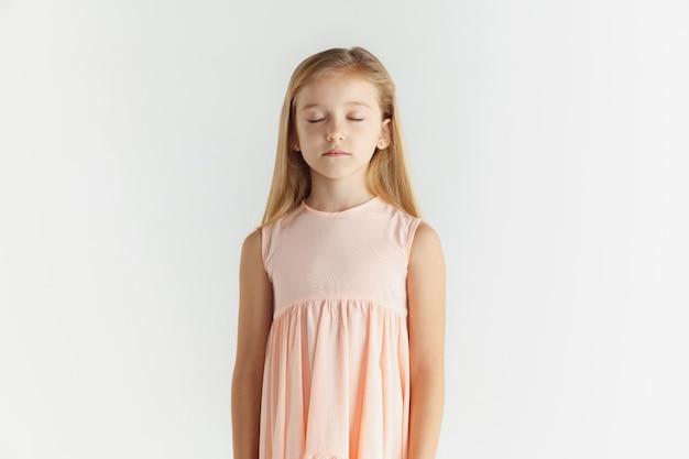 세련 된 작은 웃는 소녀 흰색 스튜디오 배경에 고립 된 드레스에 포즈. 백인 금발 여성 모델. 인간의 감정, 표정, 어린 시절. 눈을 감고 서서 침착 해 보인다.