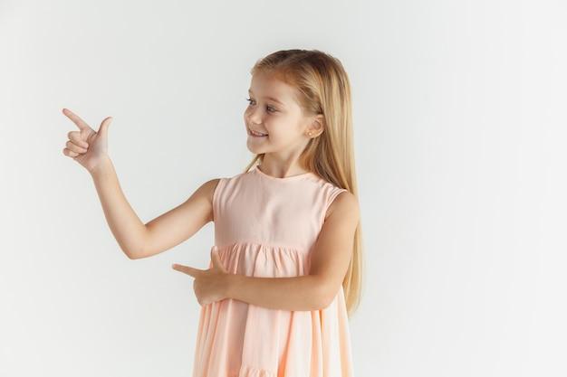 白いスタジオの背景に分離されたドレスでポーズをとってスタイリッシュな小さな笑顔の女の子。白人の金髪女性モデル。人間の感情、表情、子供時代。空のスペースバーを指しています。