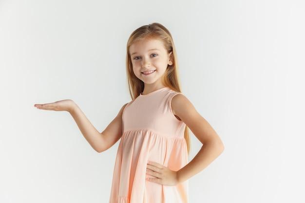 白いスタジオの背景に分離されたドレスでポーズをとってスタイリッシュな小さな笑顔の女の子。白人の金髪女性モデル。人間の感情、表情、子供時代。空のスペースバーに表示しています。