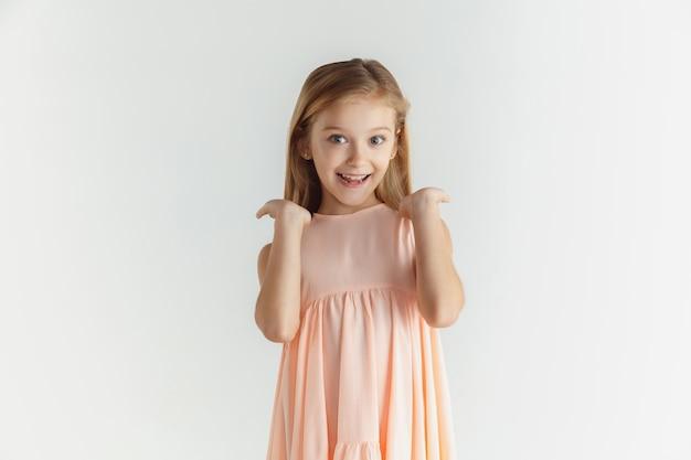 세련 된 작은 웃는 소녀 흰색 스튜디오 배경에 고립 된 드레스에 포즈. 백인 금발 여성 모델. 인간의 감정, 표정, 어린 시절. 웃고, 놀랐고, 궁금했다.