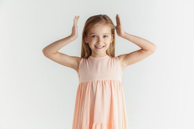 白いスタジオの背景に分離されたドレスでポーズをとってスタイリッシュな小さな笑顔の女の子。白人の金髪女性モデル。人間の感情、表情、子供時代。笑顔で、頭の近くで手を踊ります。