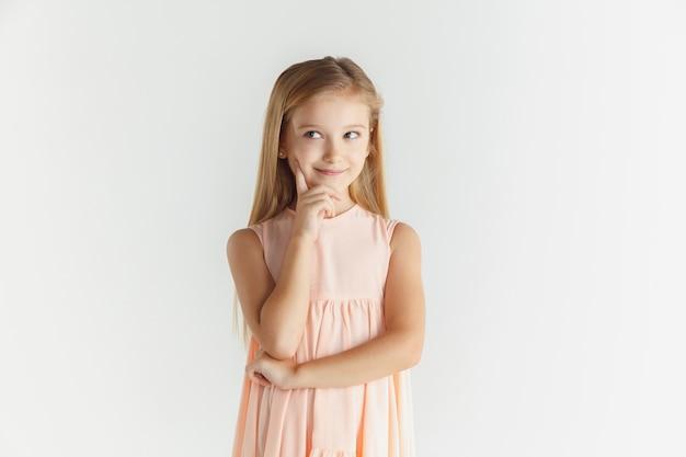 Стильная маленькая улыбающаяся девочка позирует в платье, изолированном на белом фоне студии. кавказская блондинка женская модель. человеческие эмоции, мимика, детство. думая или мечтаю,