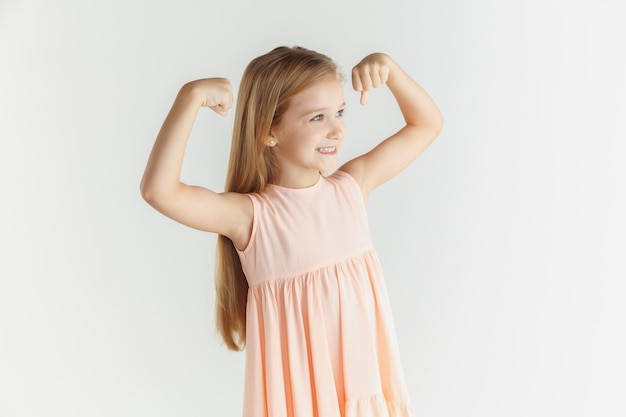 세련 된 작은 웃는 소녀 흰색 스튜디오 배경에 고립 된 드레스에 포즈. 백인 금발 여성 모델. 인간의 감정, 표정, 어린 시절. 승리, 축하, 행복해 보입니다.