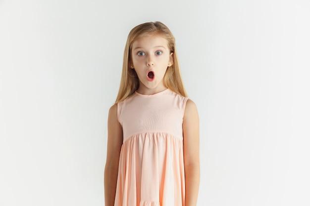 세련 된 작은 웃는 소녀 흰색 스튜디오 배경에 고립 된 드레스에 포즈. 백인 금발 여성 모델. 인간의 감정, 표정, 어린 시절. 놀라고, 놀라고, 충격을 받았습니다.