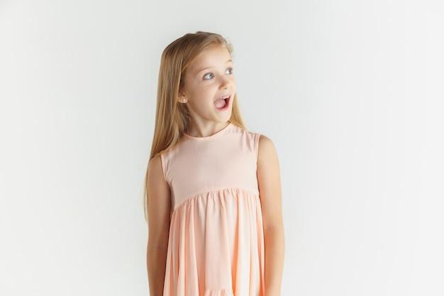 白いスタジオの背景に分離されたドレスでポーズをとってスタイリッシュな小さな笑顔の女の子。白人女性モデル。人間の感情、表情、子供時代。不思議に思って、驚いて、ショックを受けました。横を見てください。