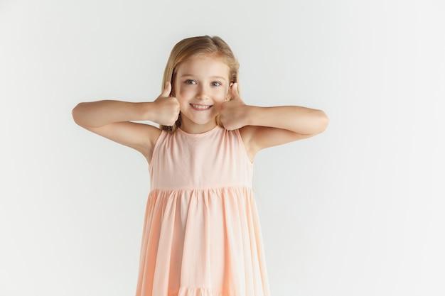 白い壁に隔離のドレスでポーズをとってスタイリッシュな小さな笑顔の女の子。白人の金髪女性モデル。人間の感情、表情、子供時代。落ち着いて見え、いい兆しを見せています。
