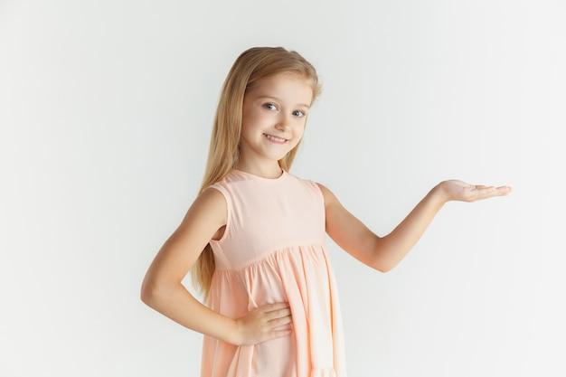 白い壁に隔離のドレスでポーズをとってスタイリッシュな小さな笑顔の女の子。白人の金髪女性モデル。人間の感情、表情、子供時代。空のスペースバーに表示しています。
