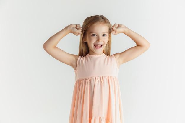 Стильная маленькая улыбающаяся девочка позирует в платье, изолированном на белой стене. кавказская блондинка женская модель. человеческие эмоции, мимика, детство. улыбается, побеждает, празднует.