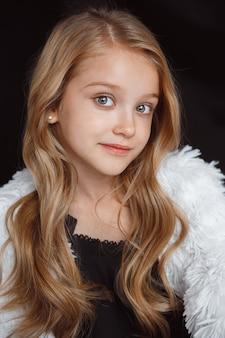 검은 스튜디오 배경에 고립 된 흰색 옷을 입고 포즈를 취하는 세련 된 작은 웃는 소녀. 아름 다운 백인 금발 여성 모델의 포즈. 인간의 감정, 표정, 어린 시절, 패션, 스타일.