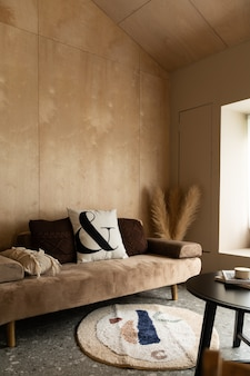 Stylish living  corner with velvet tan color sofa setting with soft pillows with plywood wall on the background / cozy interior design / modern interior