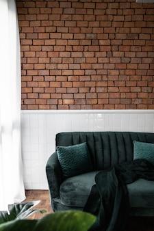 緑のベルベットのソファと人工植物で飾られたスタイリッシュなリビングルームのコーナー