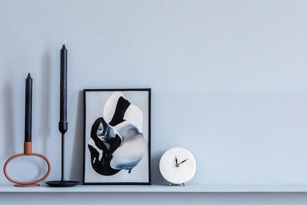 エレガントなアパートのスタイリッシュなリビング ルームのインテリアで、フレーム、白い時計、キャンドル、グレーの木の羽目板、モダンなホームステージングの棚にエレガントなアクセサリーが置かれています。
