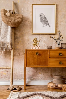 Stylish living room with vintage commode, gold photo frame, wooden ladder, bag, plaid, decoration, grunge wall and elegant personal accessories in modern retro home decor.