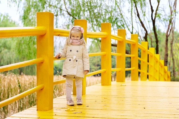 Stylish llittle girl on a yellow bridge in the park